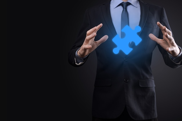 Biznesmen trzyma w rękach kawałek układanki