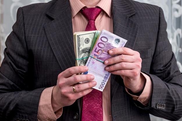 Biznesmen trzyma w rękach paczkę dolarów i euro