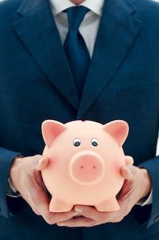 Biznesmen trzyma w rękach skarbonkę symbol oszczędności i dobrych inwestycji