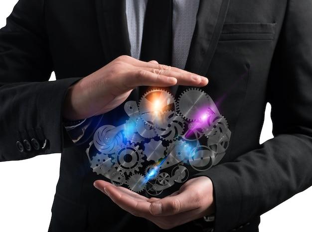 Biznesmen trzyma w rękach system mechanizmu przekładni