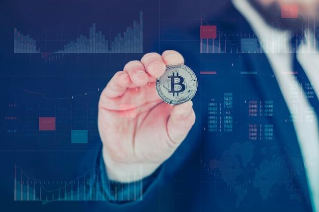 Biznesmen trzyma w rękach złotą monetę bitcoin. holograficzny panel informacyjny ze statystykami pokazuje upadek i wzrost kryptowaluty.