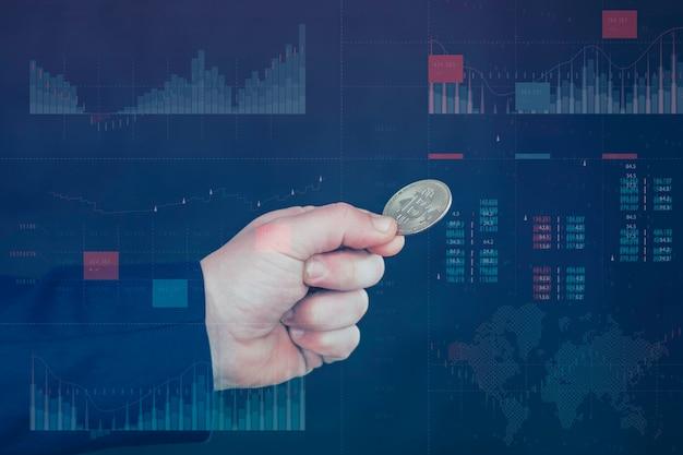 Biznesmen trzyma w rękach złotą monetę bitcoin. informacyjny panel holograficzny ze statystykami pokazuje upadek i wzrost kryptowaluty. koncepcja wirtualnej waluty i blockchain.