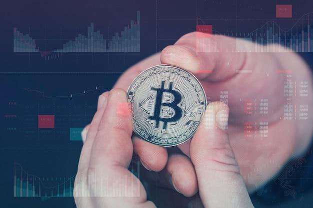 Biznesmen trzyma w rękach złotą monetę bitcoin.