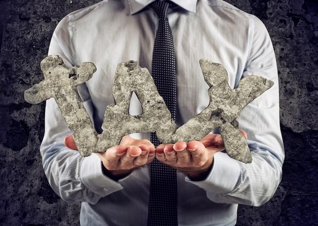 Biznesmen trzyma w ręku słowo podatek z ciężkiego kamienia