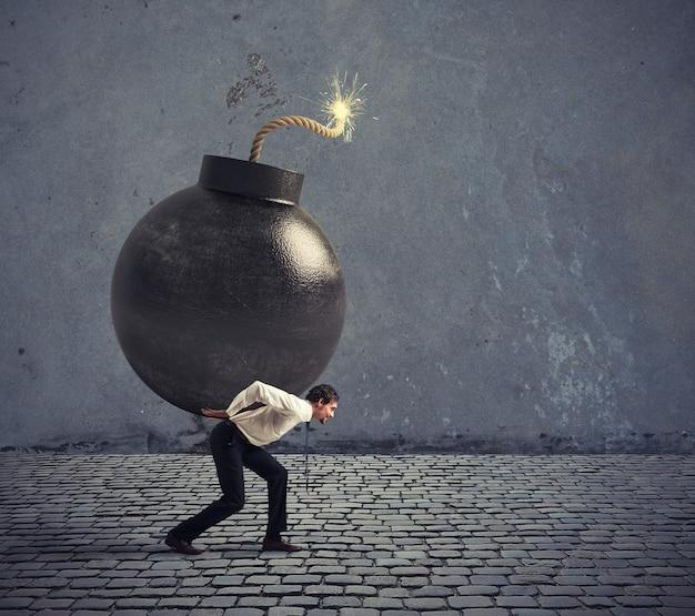 Biznesmen trzyma wielką bombę. pojęcie trudnej kariery i porażki