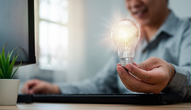 Biznesmen trzyma żarówkę i czuje się szczęśliwy dzięki nowym innowacjom i pomysłom na panele biznesowe sukcesu.