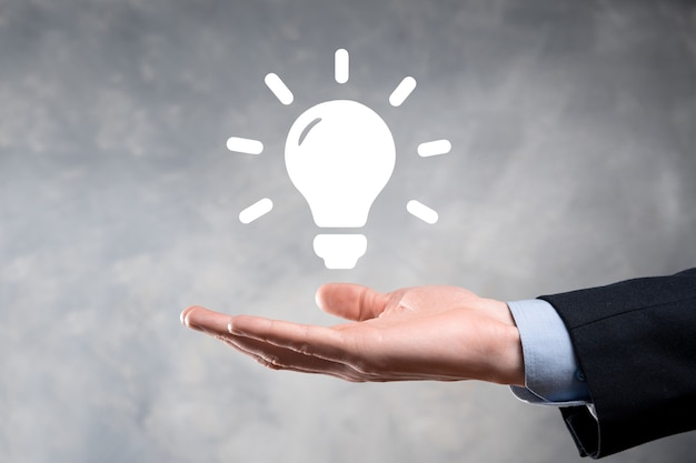 Biznesmen trzyma żarówkę. rozwiązania energetyczne.