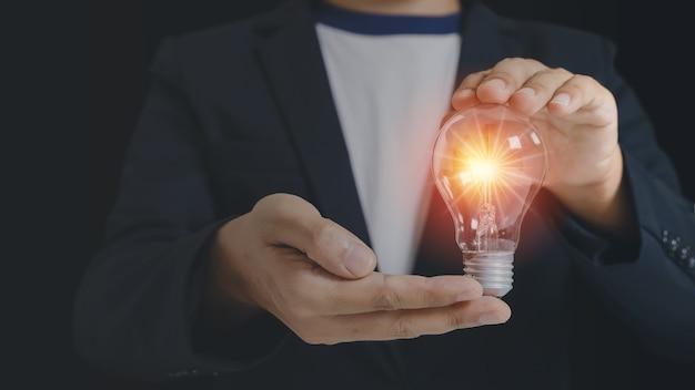 Biznesmen trzyma żarówkę z lekkim racą. kreatywne pomysły genialne innowacje wiedza sukces. symbol myślenia koncepcja twórcza.
