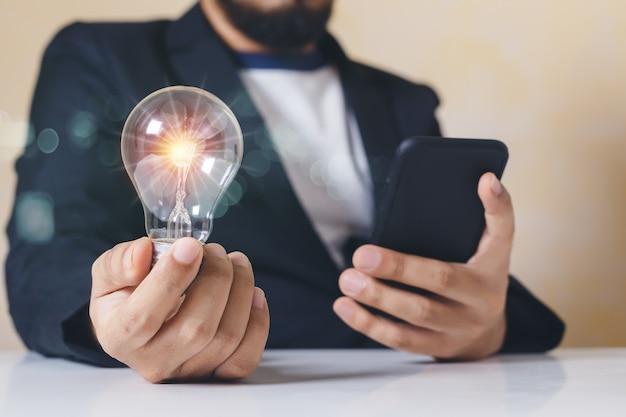 Biznesmen trzyma żarówkę za pomocą smartfona. twórczy geniusz innowacji wiedza udana. symbol myślenia koncepcja twórcza.
