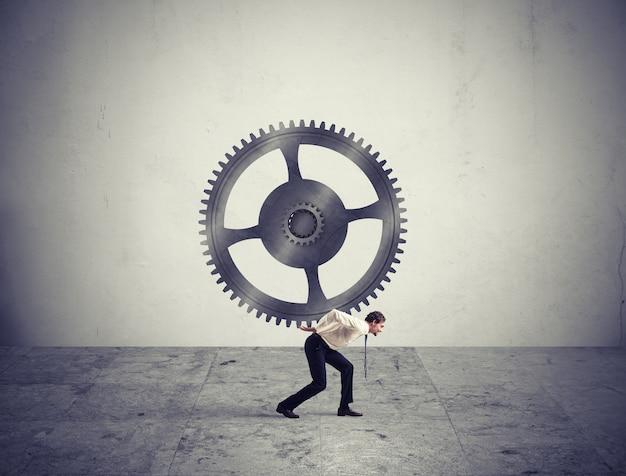 Biznesmen trzyma ze zmęczeniem duży bieg