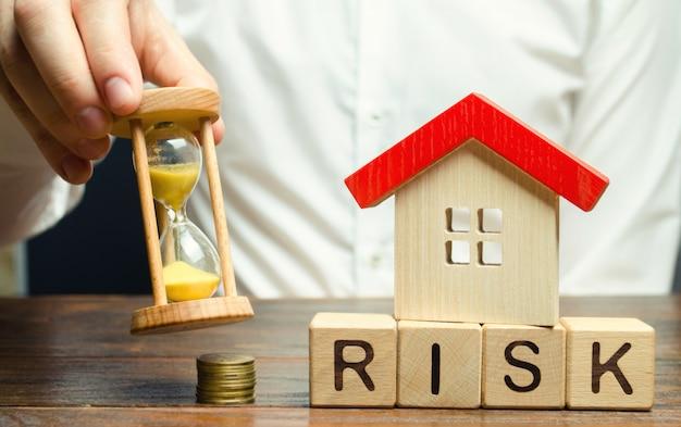 Biznesmen trzyma zegar, drewniany dom. ryzyko