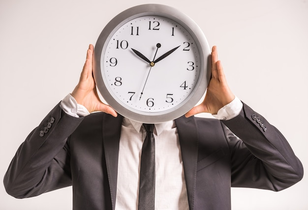 Biznesmen trzyma zegar przed głową.