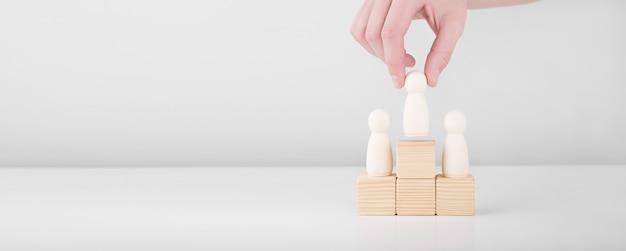 Biznesmen trzymać drewniany człowiek reprezentujący lidera wkracza do sukcesu stojąc na cokole. koncepcja przywództwa i rozwoju kariery. copyspace.