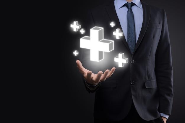Biznesmen trzymać ikonę 3d plus, człowiek trzymać w ręku oferują pozytywne rzeczy, takie jak zysk, korzyści, rozwój, csr reprezentowane przez znak plus. ręka pokazuje znak plus.