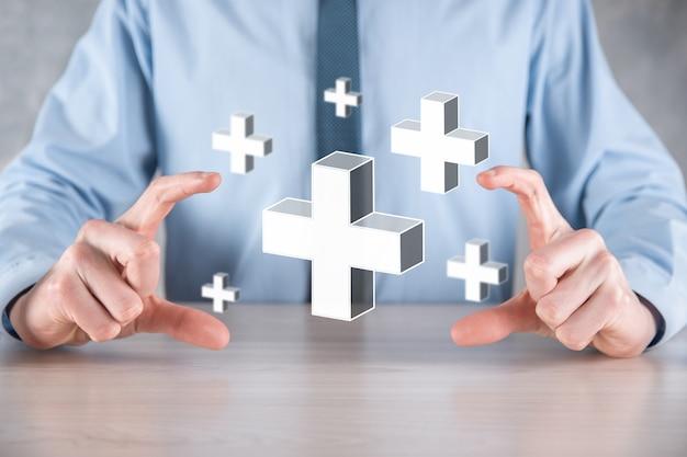 Biznesmen trzymać ikonę 3d plus, człowiek trzymać w ręku oferuje pozytywne rzeczy, takie jak zyski