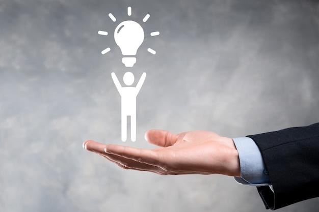 Biznesmen trzymać ikonę człowieka z żarówkami, pomysły nowych pomysłów z innowacyjną technologią i kreatywnością. koncepcja kreatywności z żarówkami, które świecą brokatem.