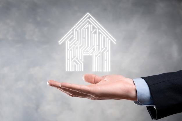 Biznesmen trzymać ikonę domu. koncepcja aplikacji inteligentnego domu sterowanego, inteligentnego domu i automatyki domowej. projekt pcb i osoba z inteligentny telefon. koncepcja sieci internet technologii innowacji.