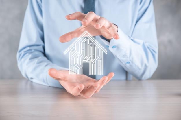 Biznesmen trzymać ikonę domu. koncepcja aplikacji inteligentnego domu sterowanego, inteligentnego domu i automatyki domowej