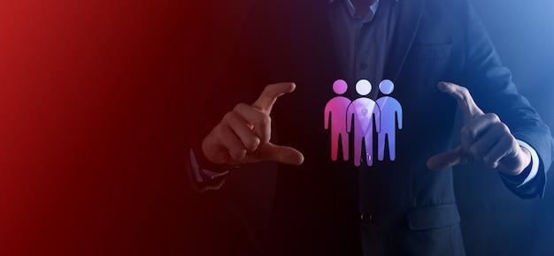 Biznesmen trzymać ikonę pracy zespołowej. budowanie silnego zespołu. ludzie ikona. zasoby ludzkie i koncepcja zarządzania. sieci społecznościowe, koncepcja centrum oceny, audyt osobisty lub koncepcja crm.