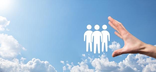 Biznesmen trzymać ikonę pracy zespołowej. budowanie silnego zespołu. ludzie . koncepcja zarządzania zasobami ludzkimi