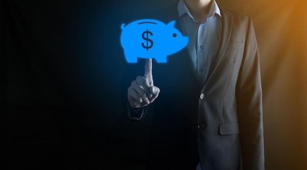 Biznesmen trzymać symbol skarbonki. planowanie wydatków biznesowych i pieniędzy i budżet inwestycyjny, koncepcja oszczędzania pieniędzy biznesowych. zapisanie lub inwestycja.