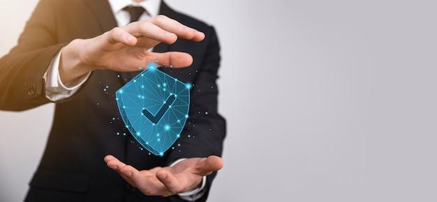 Biznesmen trzymać tarczę low poly wielokąta z ikoną kleszcza. bezpieczny dostęp do systemu concept.business finansowej gwarancji dla koncepcji investment.antivirus.technology security.protection network,safe data.