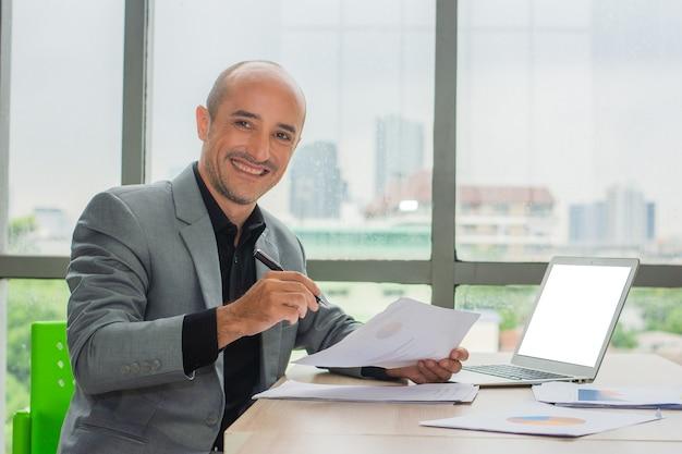 Biznesmen trzymaj długopis uśmiech w biurze, biznesmen uśmiech szczęśliwy, trader online kryptowaluta sukces