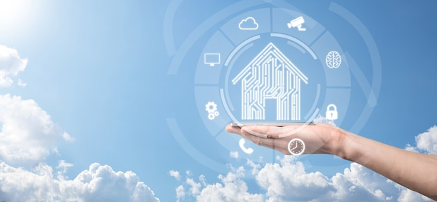 Biznesmen trzymaj ikonę domu. inteligentny dom kontrolowany, inteligentny dom i koncepcja aplikacji automatyki domowej. projekt pcb i osoba z inteligentnym telefonem. koncepcja sieci internetowej innowacji technologii.