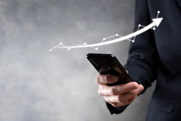 Biznesmen trzymaj rysunek na ekranie rosnącym wykresie, strzałka symbolu wzrostu dodatniego. wskazując na wykresie kreatywnego biznesu ze strzałkami w górę. koncepcja rozwoju finansowego, biznesowego.