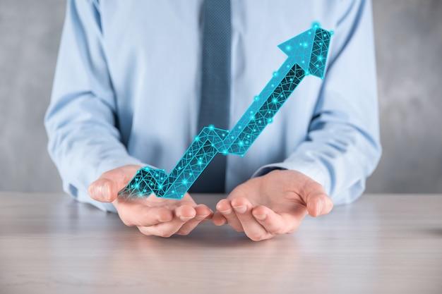 Biznesmen trzymaj wykres, strzałka ikony pozytywnego wzrostu. wskazując na wykres kreatywnego biznesu ze strzałkami w górę. finanse, koncepcja rozwoju biznesu. niska wielokąta. zwiększona sprzedaż lub zwiększona wartość.