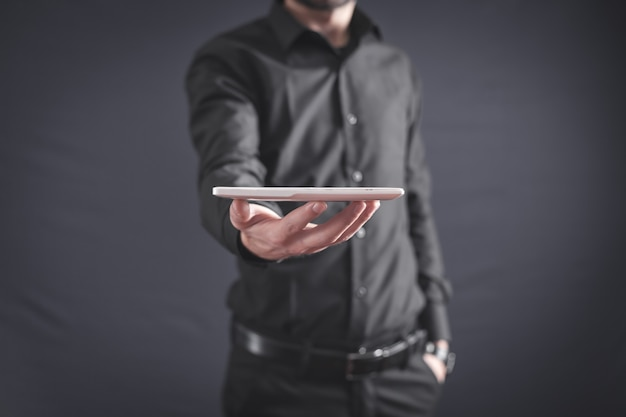 Biznesmen trzymając biały cyfrowy tablet.