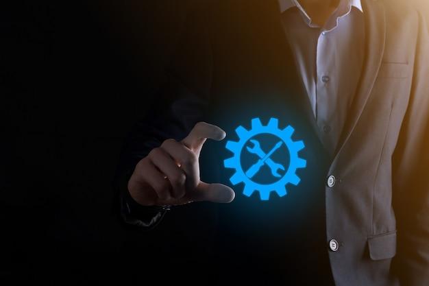 Biznesmen, trzymając ikonę koła zębatego z narzędziami. przekładnia. koncepcja cyfrowego diagramu ostrości docelowej, interfejsy wykresów, ekran wirtualnego interfejsu użytkownika, sieć połączeń.