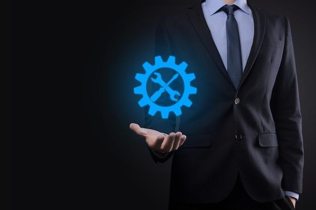 Biznesmen, trzymając ikonę koła zębatego z narzędziami. przekładnia. koncepcja cyfrowego diagramu ostrości docelowej, interfejsy wykresu, ekran wirtualnego interfejsu użytkownika, sieć połączeń.