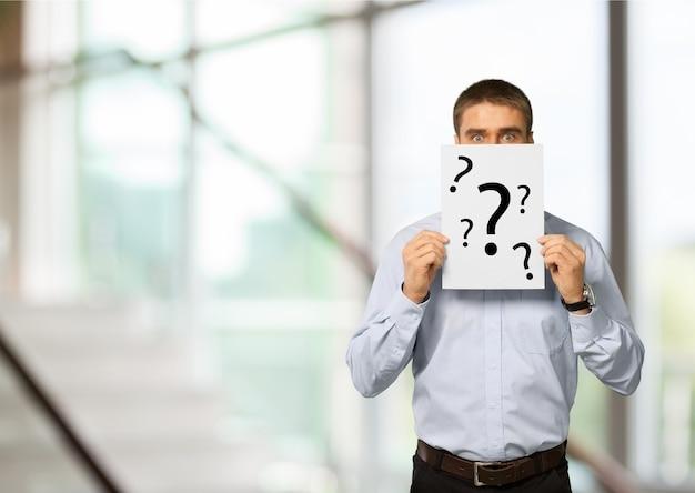 Biznesmen trzymając papier pokazują znaki zapytania na tle