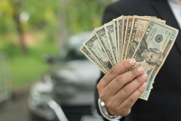 Biznesmen trzymając pieniądze w ręku stoją z przodu samochód przygotować płatność w ratach - ubezpieczenie, pożyczka i zakup samochodu