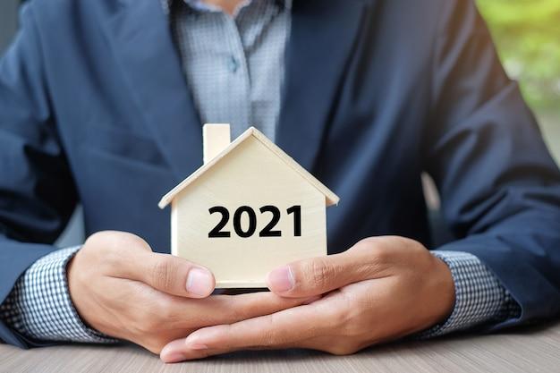 Biznesmen trzymając się za ręce, trzymając drewniany model domu z 2021 r
