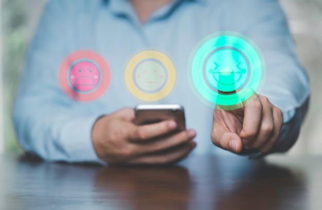 Biznesmen, trzymając smartfon i dotykając uśmiech twarz ikona