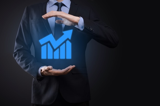 Biznesmen trzymając tablet i pokazujący rosnący wirtualny hologram statystyk, wykresu i wykresu ze strzałką w górę na ciemnym tle. giełda papierów wartościowych. koncepcja rozwoju, planowania i strategii biznesowej.