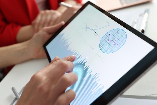 Biznesmen trzymając tablet z wykresami i diagramami w rękach w miejscu pracy