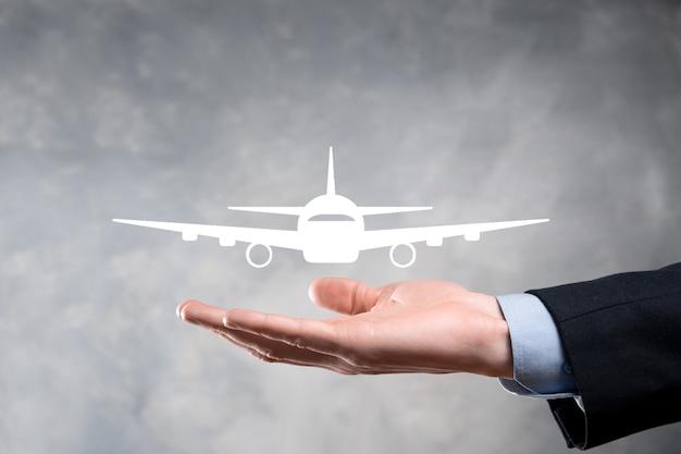 Biznesmen, trzymając w rękach ikonę samolotu. zakup biletów online. podróż.