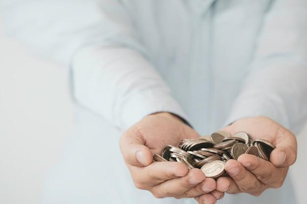 Biznesmen, trzymając w ręku monety, zysk z inwestycji i pieniądze z dywidendy z oszczędności koncepcji.