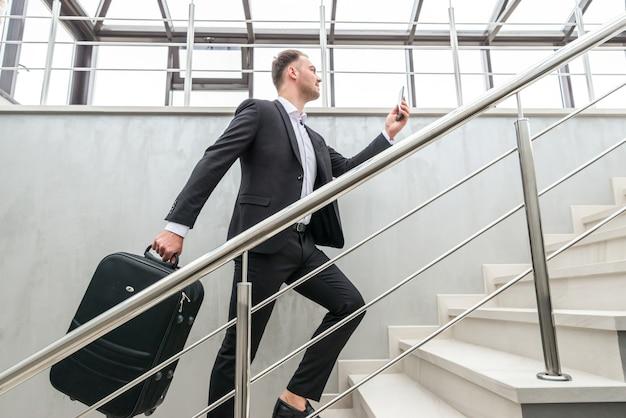 Biznesmen trzymając walizkę na schodach w nowoczesnym budynku