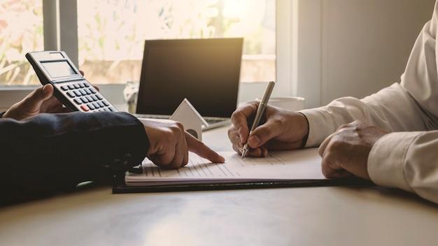 Biznesmen trzymający długopis piszący na kartce papieru umowa wypełnia formularz wniosku o kredyt hipoteczny szablon finanse koncepcja inwestycji