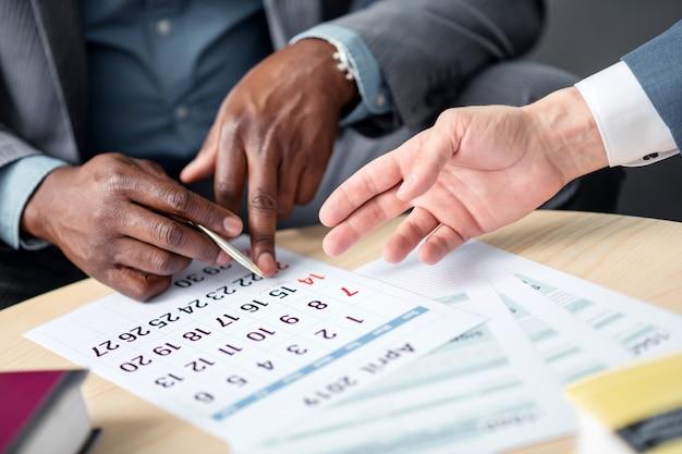 Biznesmen trzymający długopis zbliżenie ciemnoskórego biznesmena trzymającego długopis podczas planowania spotkania z kolegą