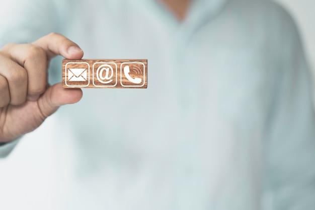 Biznesmen trzymający drewniany klocek, który drukuje na ekranie, kontakt biznesowy zawiera adres e-mail i numer telefonu.