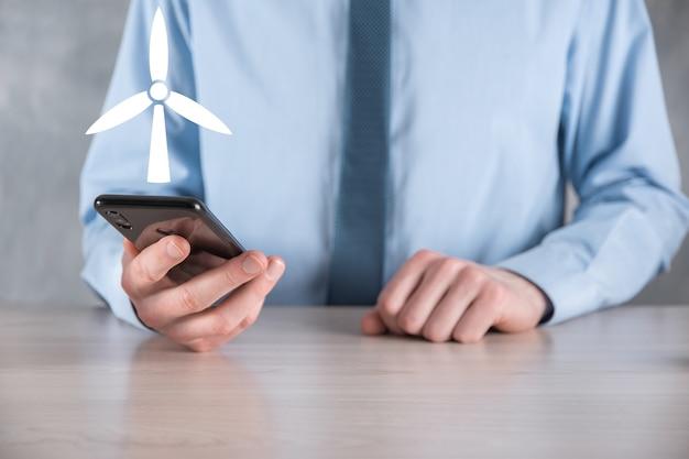 Biznesmen trzymający ikonę wiatraka, który wytwarza energię środowiskową