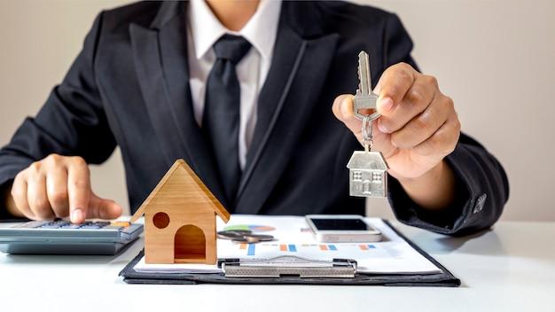Biznesmen trzymający klucze do domu i drewniany model domu umieszczony na papierach koncepcja finansowa