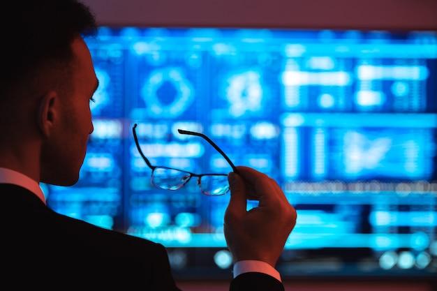 Biznesmen trzymający okulary na tle ekranu