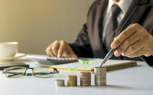 Biznesmen trzymający pióro i drzewo rosnące na monecie, planujący pomysły na inwestowanie i zarabianie pieniędzy.