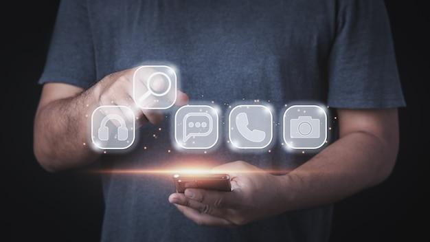 Biznesmen trzymający telefon pokazujący gest wskazujący palcem, aby nacisnąć przycisk ikony wyszukiwania